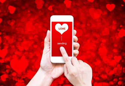 Hand holding smart phone with sending love word and heart shape